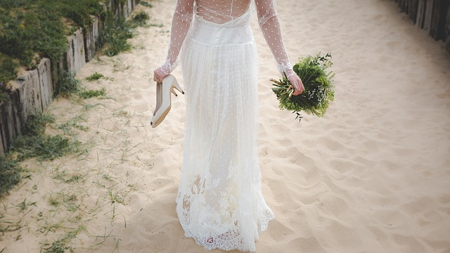 Bride carrying shoes and bouquet